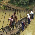 Anak sekolah melewati jembatan putus